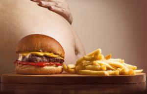 uomo mangia hamburger e patatine. Osteopatia per trattare gastrite