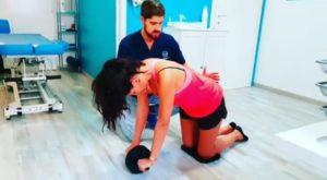 esercizi addominali con ab wheel fisioterapista aiuta ragazza a svolgere esercizio